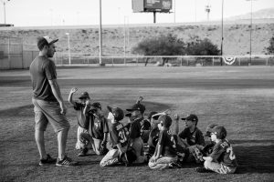 a coach with a group of yung people sat on the playing field listening to the coach